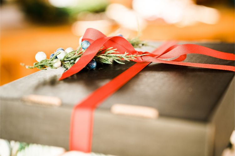 Corporate Christmas Gift in a black box with a red ribbon and Christmas decorations