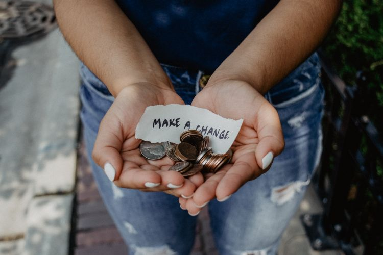 Woman holding change in palm of hands with a piece of paper that reads